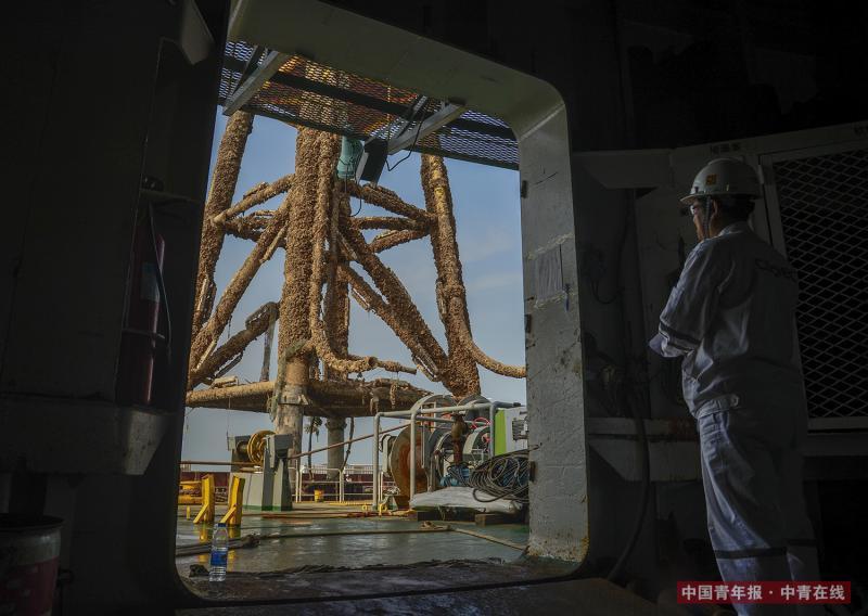 一座高30米的海洋石油平台导管架废弃后被回收上船。