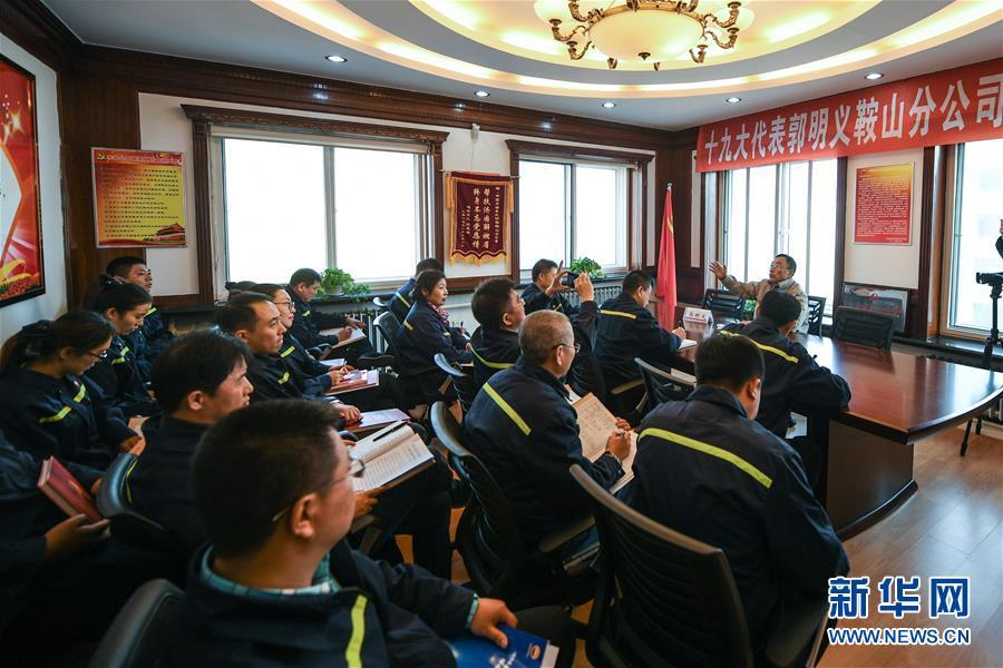11月3日,郭明义(右三)在鞍钢矿业集团齐大山铁矿采场与工友交流制定修路方案。