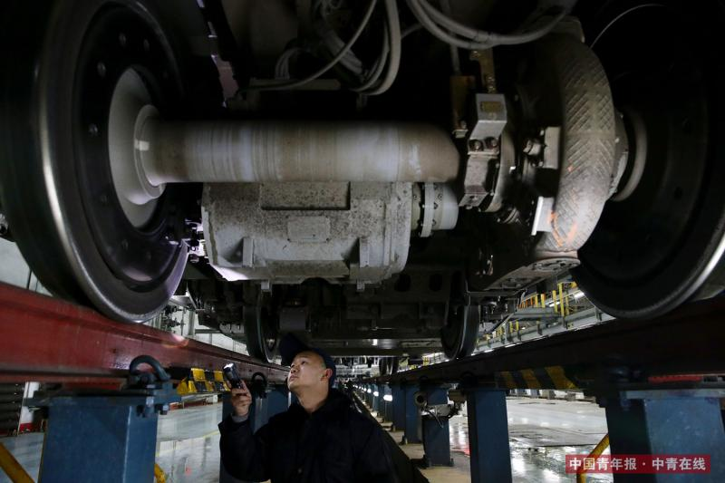 """2月2日晚,北京南动车所,为了保证动车在线路上的安全运行,机械师对""""复兴""""号动车组车底的每个细节逐一检查。当晚,完成一天春运运输任务的""""复兴""""号和""""和谐""""号动车组陆续回库检修。北京南动车所是北京动车段最大的动车检修库,配有12股检修线,可供24组动车组停留检修,也被称为动车的""""4S""""店。中国青年报·中青在线记者 陈剑/摄"""