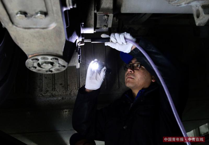 """2月2日晚,北京南动车所,机械师对""""复兴""""号动车组的齿轮箱添注润滑油。2018年春运期间,每天有包括数十组""""复兴号""""在内的80组动车组列车在北京南动车所接受检修,1500余名工人轮班连夜工作。中国青年报·中青在线记者 陈剑/摄"""