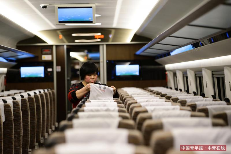 """2月2日晚,北京南动车所,""""复兴""""号动车组内,清洁工整理座椅。中国青年报·中青在线记者 陈剑/摄"""