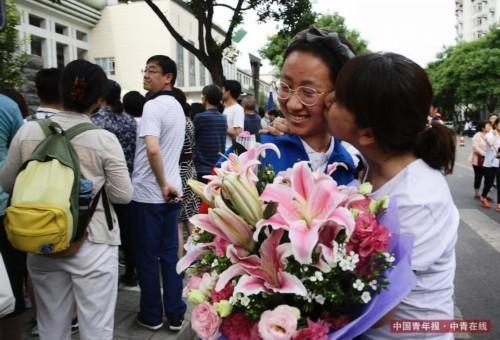 6月8日,北京东直门中学高考考点外,一位妈妈为刚刚结束考试的孩子送上鲜花,情不自禁地在女儿脸上亲了一下。当日下午,全国大部分地区高考结束,北京东直门中学高考考点外,不少家长给孩子送上鲜花,并和孩子合影留念,记录高考结束的瞬间。中国青年报·中青在线记者 陈剑/摄