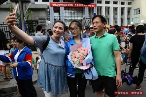 6月8日,北京东直门中学高考考点外,一位结束考试的女生手捧鲜花和父母合影留念。