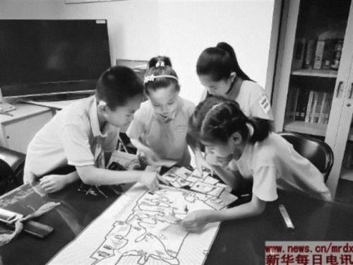 """北京市西城区小学生正在体验""""红色足迹""""游戏棋(6月26日摄)。本报记者乌梦达摄"""