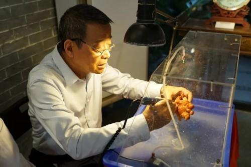 △广州玉雕国家级传承人高兆华正在用金丝玉雕刻《送子观音》(央视记者 沈忱拍摄)