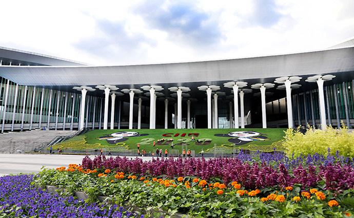 10月14日,园林工人在国家会展中心(上海)南广场进博会鲜花装饰草坪上施工。新华社 图
