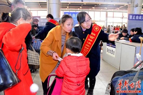 龙伟华和其他志愿者一起帮助旅客扛、挑大件行李。