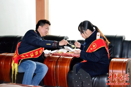 中午休息时分,龙伟华和王艳夫妻俩在休息室里吃盒饭。
